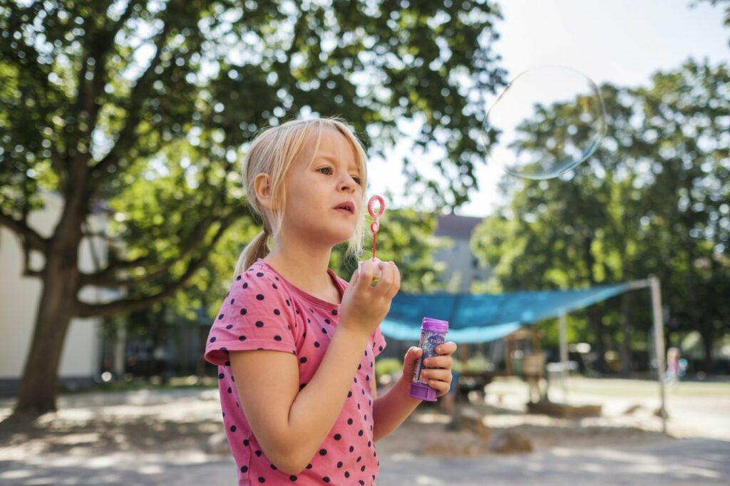 Ein Mädchen pustet Seifenblasen. - AWO Forchheim
