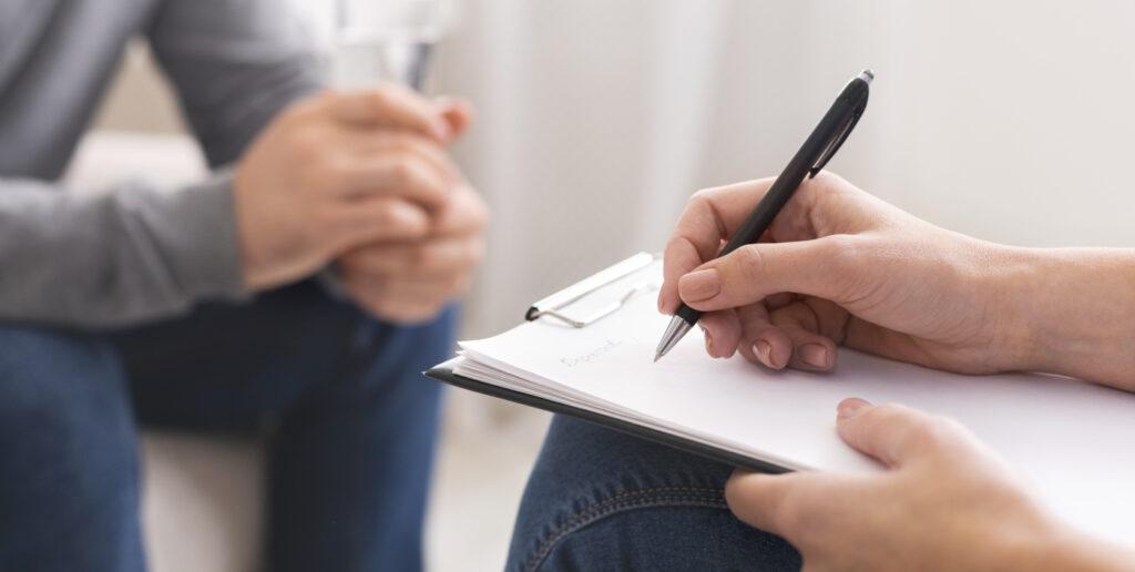 Eine Frau macht sich in einem Zweiergespräch Notizen. - AWO Forchheim