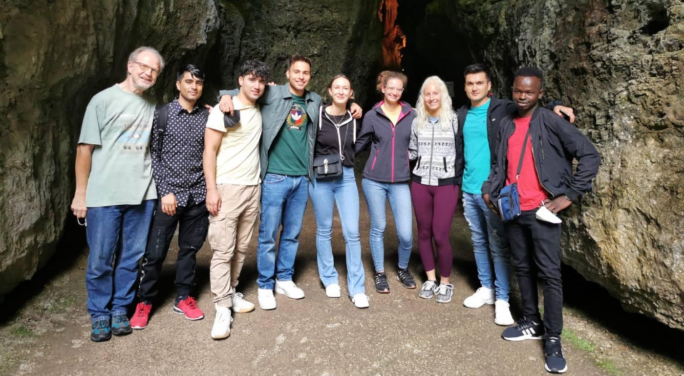 Unterschiedliche Menschen stehen vor einer Höhle. - AWO Forchheim