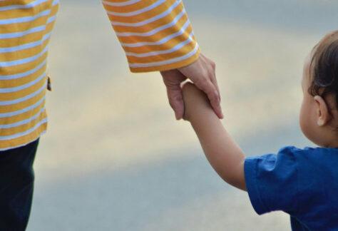 Ein Erwachsener führt ein kleines Kind an der Hand. - AWO Forchheim